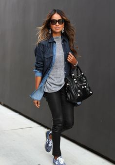 Shop this look on Lookastic: http://lookastic.com/women/looks/sunglasses-earrings-crew-neck-t-shirt-dress-shirt-watch-tote-bag-skinny-jeans-low-top-sneakers/7652 — Black Sunglasses — Silver Earrings — Grey Crew-neck T-shirt — Navy Denim Dress Shirt — Silver Watch — Black Leather Tote Bag — Black Leather Skinny Jeans — Blue Low Top Sneakers