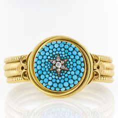 Georgian Turquoise Bracelet -- This highlight of this amazing Georgian bracelet is a mesmerizing surround of graduated turquoise beads featuring a silver star of old mine and rose cut diamonds, turning over to reveal plated woven hair. It is bordered by twisted and plain wire and constructed in 18 karat gold. The fluer de lys and snake chain bracelet of 14 karat gold