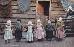 Portret van zes kinderen in Volendammer dracht voor een woonhuis. Het meisje rechts heeft een pop onder de arm en rechts achter het hek kijkt een oude vrouw toe. Voor de woning hangt wasgoed te drogen. 1900-1908 #NoordHolland #Volendam