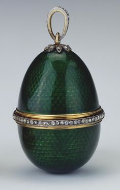 Miniature egg of dark green guilloché enamel with a diamond & gold band, and a flower & ring mount at top, the interior of white enamel, enclosing a silver-gilt, standing, winged angel holding a green leafed branch. With a gold stand. 1900