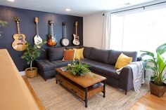 Boise Boys | Timber And Love | Luke Caldwell | HGTV | Realty | Mid Century modern | home renovation | Design | Boise Idaho | Feature Black wall | Guitar Wall | Plants | Gray Sectional