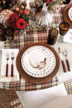 A Thanksgiving table with plaid, brown accents, and red flowers