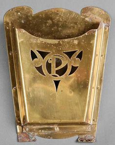 A Newcomb College brass mailbox [or mail pocket], circa 1915, hand wrought brass sheeting with cut out decoration of monogram P in a roundel flanked by scrolls. Arts and crafts design; Craftsman bungalow