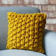 Cullompton Colour Chunky Knitted Panel Cushion. Chunky hand-knitted decorative cushion in striking charcoal black or speckled tweed neutral.Available in charcoal black or subtle grey.