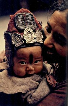 "from Ladakh - The Last Shangri-la, article and photographs by Thomas J. Abercrombie. March 1978. ""The woolen cap on a younger child guards against cold winds, while the amulets and needles that decorate it ward off evil spirits."""