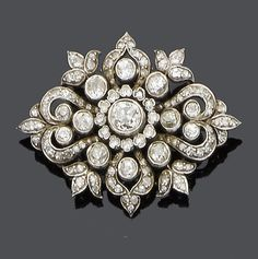 A mid 19th century diamond brooch, circa 1860 The central old brilliant-cut diamond within a single-cut diamond border, to a scroll and foliate old brilliant and single-cut diamond surround, mounted in silver and gold