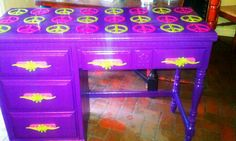 Mac's desk for the peace sign bedroom makeover. Desk was 25.00 knobs were salvaged off a 1970's dresser rotting on the side if the road.  The glittery peace signs under the glass top were 12 for 2.95 Christmas ornaments
