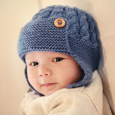 A cabled baby hat with single button chin fastening, earflaps and an aviator style front flap.  The pattern gives instructions for four sizes of baby