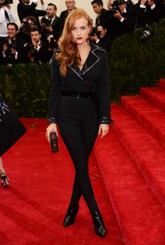 Riley Keough is wearing a custom black jumpsuit made of stretch wool and satin and embroidered with a mix of mirrors and glass tubes. The jumpsuit is belted and accessorized with Epi leather Eternal boots, a Monogram Epi Petite Malle, and a single Essential V earring. #MetGala