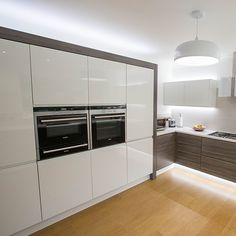 Handleless kitchen in high gloss white and contrasting walnut effect doors nestkitchens.co.uk