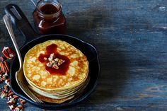 #Pancakes in pan  Stack of homemade american pancakes with pecans and chocolate caramel sauce on a cast-iron frying pan over rustic background selective focus. Delicious dessert for breakfast
