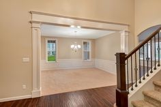 Large custom header into the formal dining room with real wainscoting and elegant lighting.