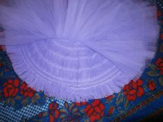 1: Another way of making a tutu. This tutu has one layer and all frills are sewn onto this same layer. (see the circles). The hoop is inserted near the last frill. There are two layers of gathered net that lay flat against the tutu skirt. This gives a fluffy appearance to this tutu. The layers can be pleated too. This tutu is good for heavy decoration.