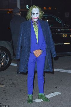 Lewis Hamilton was almost unrecognisable with a bloody slashed grin and greasy green hair as he arrived at Heidi Klum's annual Halloween party dressed as The Joker
