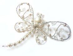 Esta libélula tiene un cuerpo de agua dulce blanco perla y perla Swarovski y cola de cristal. Es macramé con hilos de plata y cada grano se