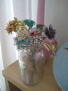 Vintage brooch floral arrangement...I would do a frosted or colored jar for the vase tho..
