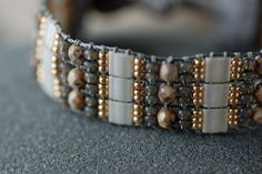 Hand-Loomed, Beaded Cuff Bracelet by EntwyneDesigns on Etsy. Gorgeous wintry pallete. Hand woven on a beading loom using Tila glass tile beads in Ivory Pearl, Czech fire-polished beads in Mineral Mosaic, gold lined gray glass and tiny gold galvanized seed beads..Ends are vegan-friendly ultrasuede. This lightweight, comfortable fashion cuff is adjustable to two sizes.