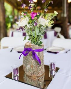 Country wedding idea: use a drilled-out log as vases for the centerpieces. They filled with flowers and set upon a centerpiece mirror.