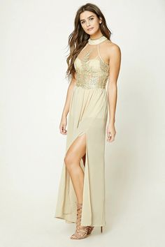 A woven chiffon maxi dress featuring a sleeveless cut, an embroidered mesh panel top with a high neckline, built-in romper underlayer, single high side slit, shirred waist, and an exposed back zipper.