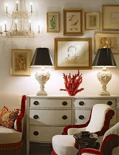 lamps with black shades, red coral, white dresser, gallery wall, white chairs with red velvet trim