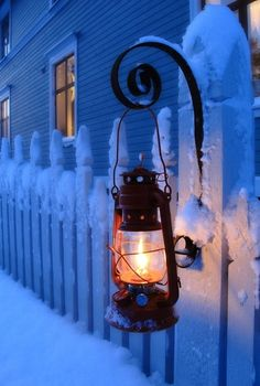 Snow, lantern, picket fences and light shining through the nighttime windows .... happy sigh