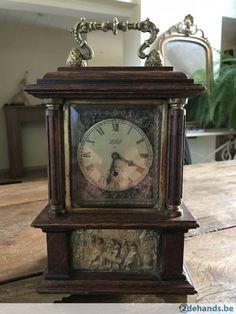 Klokje in houten kast met bronzen decoratieve plaatjes. Wekkersysteem onderaan met muziekdoosje. In werkende Staat. Hoogte 25cm -breedte15cm tel...