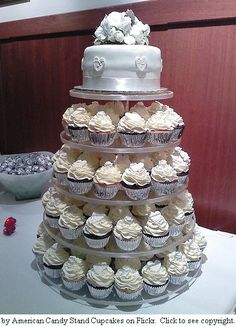 Maybe something like this, with a small cake at the top, but decorated more like the other cupcakes, with flowers and stuff.  Best of both worlds.
