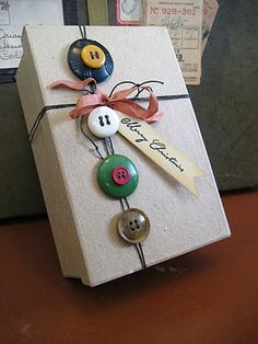 buttons tied around the christmas presents would be absolutely adorable .