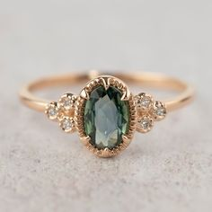 This beautiful one of a kind genuine peacock green sapphire ring is made of 100% recycled 14k rose gold. This unique engagement ring is perfect for the anything-but-traditional bride. A unique peacock green sapphire ring will also be the perfect birthday gift for those born in