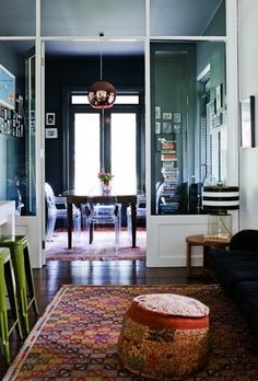 dining room, ghost chairs, Tom Dixon copper pendant, kilim rug & pouf, dark walls, mini gallery walls, green stools, black/white striped lampshade