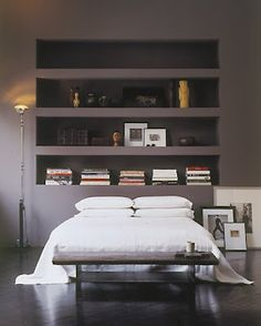 Built in storage shelves above the bed as a headboard.