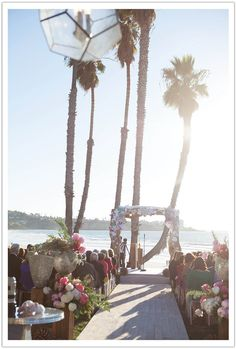 California Beachside Seaside wedding ceremony with driftwood chuppah layered with various shaped origami, ghost chairs, underwater inspired textured flowers on mother of pearl vases on rustic wooden pillars. Chic and sophisticated with beachy and zen undertones, along with understated Asian and oceanic influences. Design by Alchemy Fine Events www.alchemyfineevents.com    Modern Luxe La Jolla Beach Wedding by Alchemy Fine Events, part 1  www.alchemyfineevents.com
