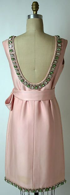 Pale pink silk cocktail dress - circa 1968.  Mini sheath dress.  Sleeveless; belted with a wide sash belt.  The high neckline falls dramatically in the back to the waist - creating a backless expanse.  The neckline is trimmed, as well as the hemline - with a row of glass jewels and rhinestones.....