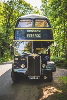 Blue double Decker London Bus - Image by Photography34 - A rustic styled low budget DIY wedding with outdoor venue, handmade bridal gown and handmade bridesmaid dresses. High street tweed groomsmen and dove grey colour scheme.