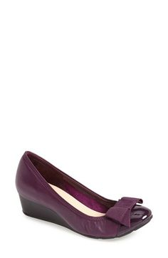 Free shipping and returns on Cole Haan 'Air Tali' Wedge Pump (Women) at Nordstrom.com. A grosgrain bow and a patent-glossed cap toe bring ladylike sophistication to a stylish pump that features an elastic-perfected fit. The modest wedge heel provides demure lift, and is deceptively comfortable thanks to a cushioned sole enhanced with Nike Air® technology. <br><br>Founded in Chicago, Illinois in 1928, Cole Haan is known for producing stylish, classic shoes with an emphasis on comfort.