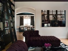 Chic espresso brown & purple office den with gray walls paint color, purple velvet tufted chaise lounges and black built-ins bookshelves.