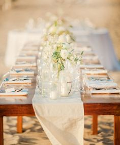 Wood table, linen runner, low white centerpieces, mason jar candles, beach reception. Photography by amandawilcher.com, Event   Floral Design, Planning   Decor by thedazzlingdetails.com