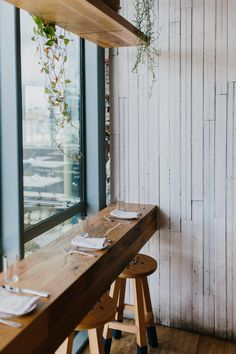 reclaimed wood bar with simple counter bar stools and crawling vines and plants. Love the whitewashed boards! (From Cafe NoSe at South Congress Hotel in Austin)