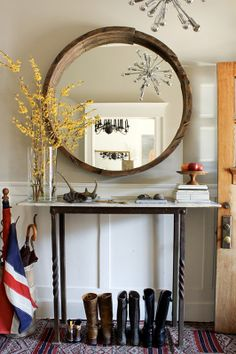 earthy entry.  rustic wood mirror, paneling, sputnik chandelier, and iron console.
