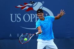 Bernard Tomic of Australia returns a shot against Carlos Berlocq of Argentina during their men's single first round match on Day Two of the 2012 US Open