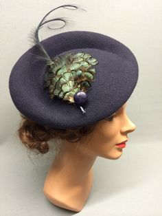 The Pearl! A large round felt fascinator with attached integral hairband. The Pearl is distinctively asymmetric in shape with a thicker brim at the back and a circular dipped crown. Elegantly trimmed with a sleek feather pad, vintage button and long curved feather. Colour: Navy #Fabhatrix #Edinburgh #Grassmarket #felt #fascinator #occasion