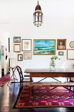 This dining room has all the makings of a boho-inspired space: antique furniture, a colorful kilim, and an eclectic gallery wall. The Moroccan-inspired lantern adds a global element and draws the eye up