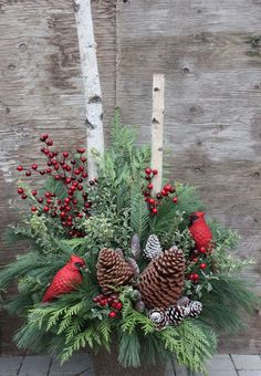 winter urn arrangement with pinecones, red berries and cardinals