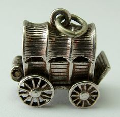 1960s opening silver covered wagon charm with hat and gun, outside/closed view (£28)