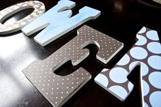 A great DIY guide on how to make nursery letters for the babys name using scrapbook paper and mod podge
