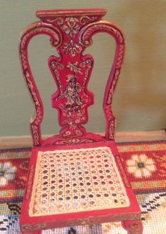 """A beautiful example of Janet Reyburn's wonderful furniture. A red chinoiserie chair with a hand caned seat. This lovely chair is 3 3/4"""" tall with delicate painting in gold and black on the lacquer red ground. The and caned seat is. Done in very fine linen thread. This chair is listed for $495 on another site. 
