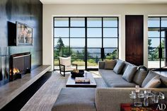 Tom Kundig of Olson Kundig Architects applied his industrial aesthetic to the family room in this Portland, Oregon, home. Blackened-steel panels sheathe the fireplace wall; a concrete slab forms a minimalist hearth. The furnishings and rug echo the colors and forms of Kundig's architecture. (December 2010)
