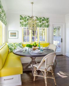 David Duncan Livingston Photography - Charming yellow and green breakfast nook is fitted with a white l-shaped banquette accented with canary yellow cushions complemented with green leaf pattern pillows placed beneath yellow framed windows dressed in green leaf pattern roman shades.