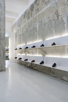 The simple use of colour and materials, like white shelves, and accented lights with the old structure of bare walls and concrete, has a striking result.