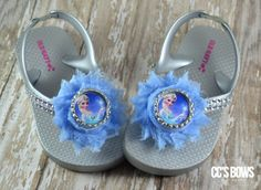 Silver flip flops embellished with rhinestones on the straps along with a light blue shabby flower and an Elsa bottle cap in the middle.  Please specify size needed when ordering!
